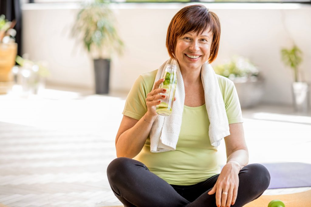 a white or perhaps Latina middle aged woman smiling and sitting on the floor with a towel and a bottle of water after exercising
