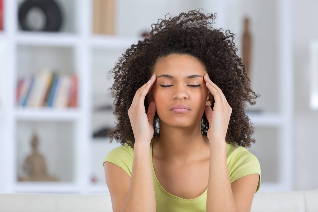 a young Black woman with her eyes closed and looking like she has a headache, or is medicating, rubbing her forehead