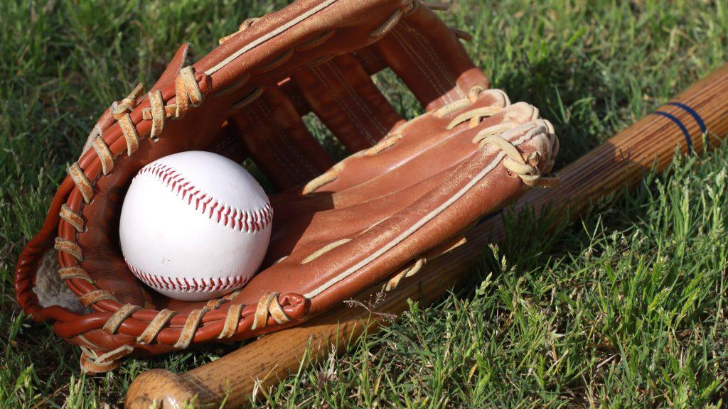 bate de béisbol, pelota y guante sobre césped