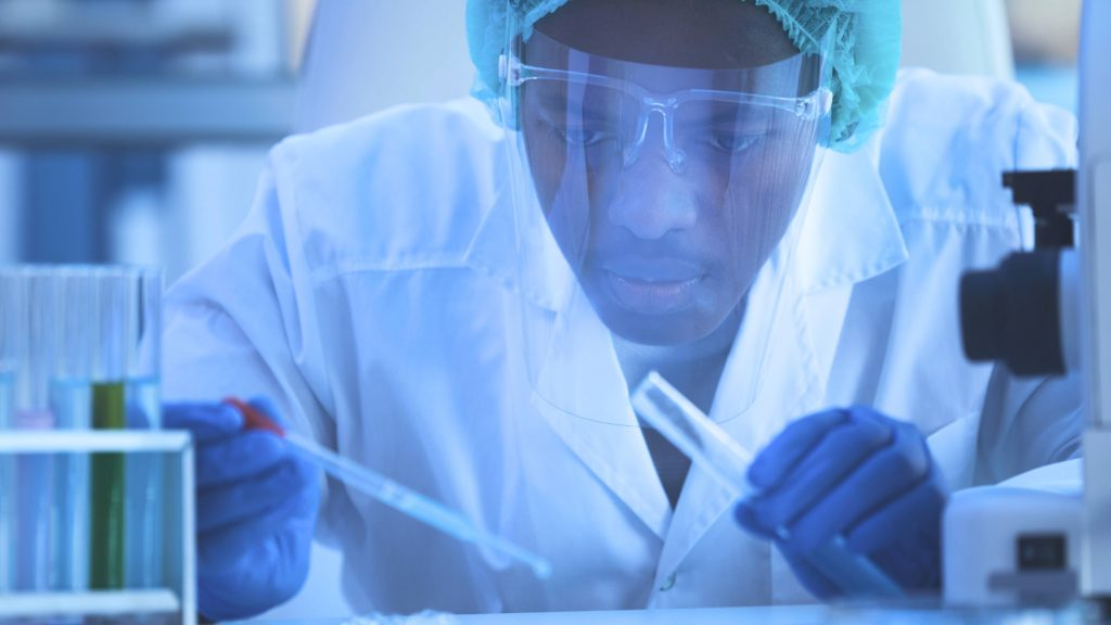 a Black man wearing goggles and other protective medical equipment in a research laboratory working with vials and tubes