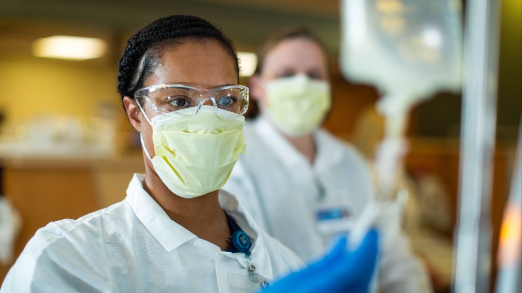 a Black woman wearing protective eye goggles and a face mask in a Mayo Clinic clinical hemodialysis technician program working with testing bags