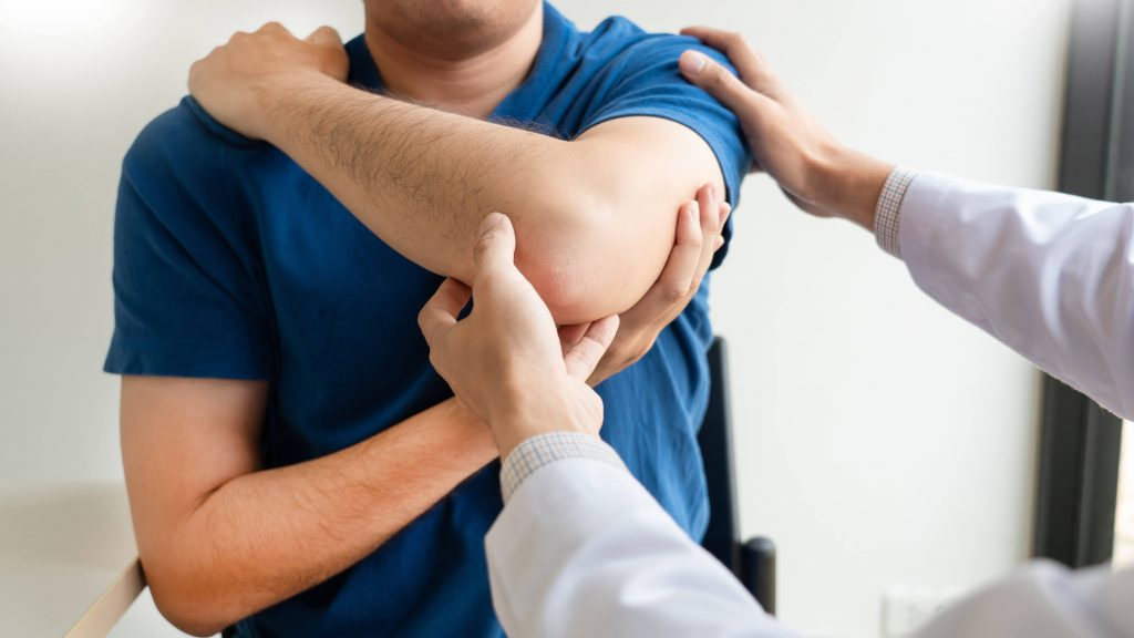 a white man in a blue shirt holding up his sore left arm, in pain, perhaps an injured shoulder or elbow, with a medical person examining the injury