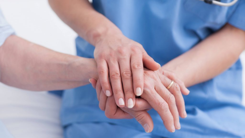 a white medical staff person in blue scrubs holding the hand of a white patient showing concern and care