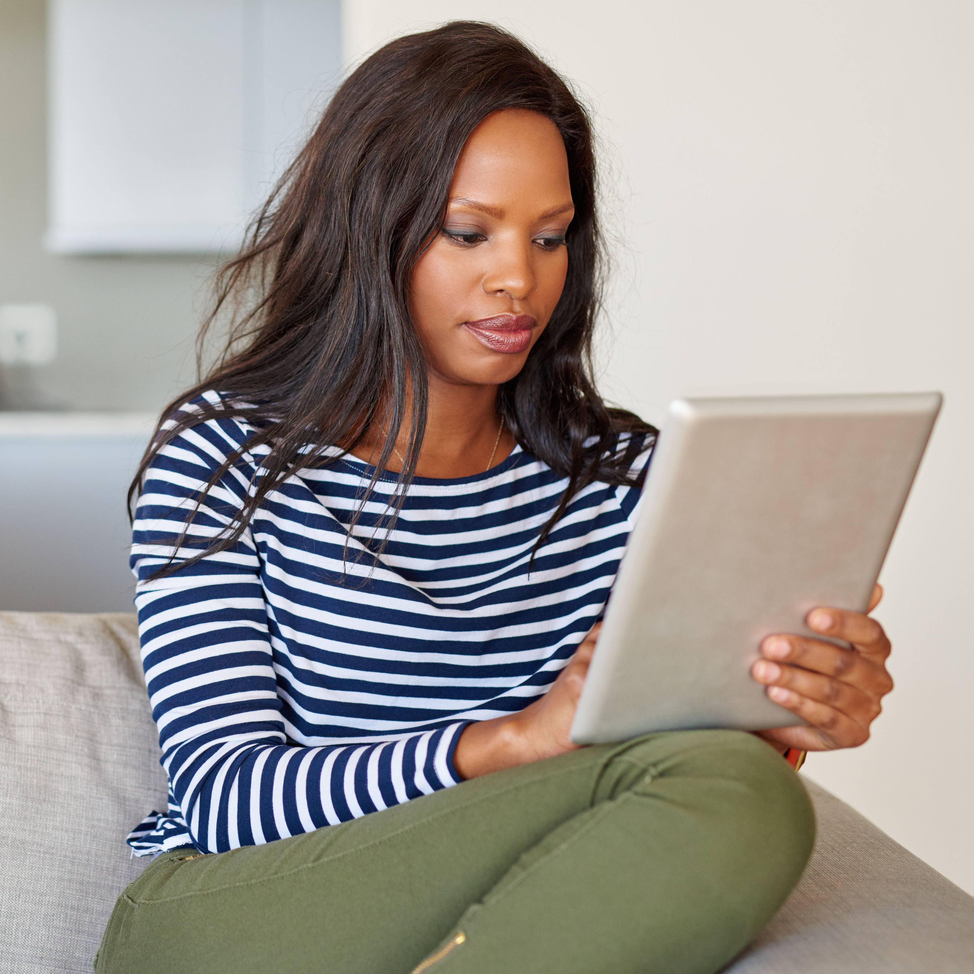 a young or middle aged Black woman curled up on a couch and reading information on a computer iPad or tablet