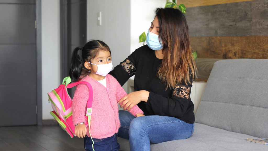 a young, perhaps Latina woman, sitting on a couch helping a little Latina girl, maybe her daughter, get ready for school a adjusting her backpack and both wearing face masks
