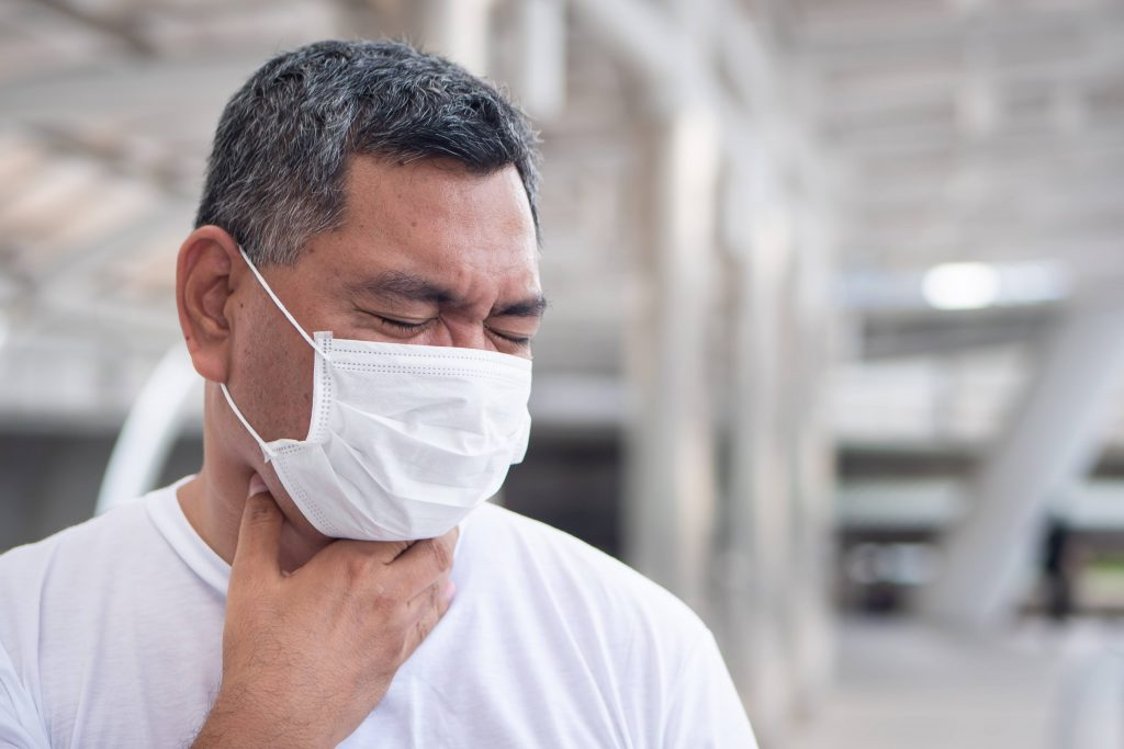 a middle aged man, perhaps Latino, with black and gray hair and wearing a white mask while wincing in pain and holding his hand to his throat