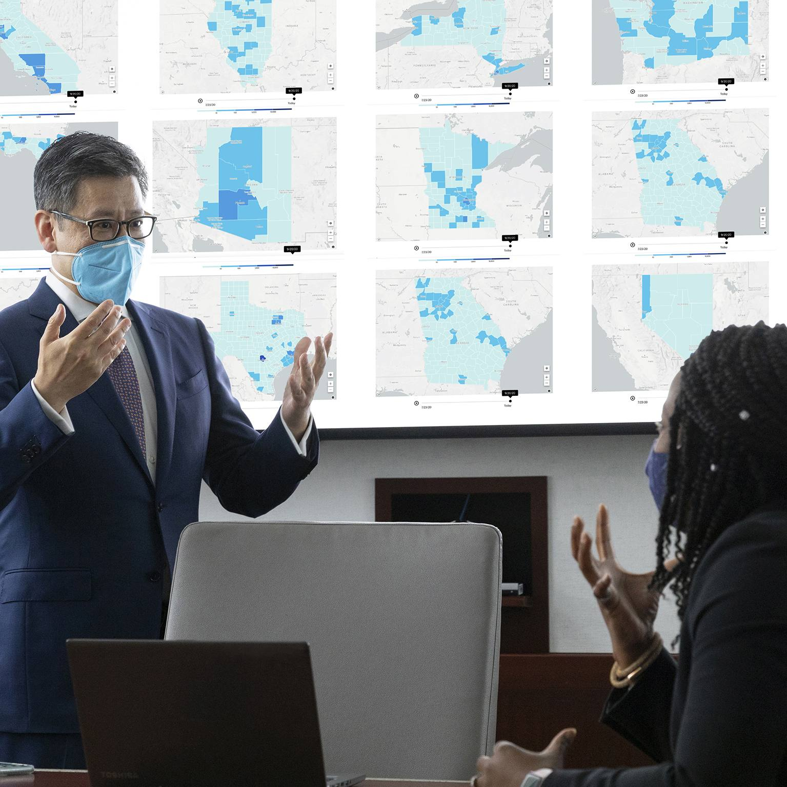 Dr. Ting with research team, wearing face masks, viewing and talking about the large wall monitors displaying maps of the states on the coronavirus tracking tool