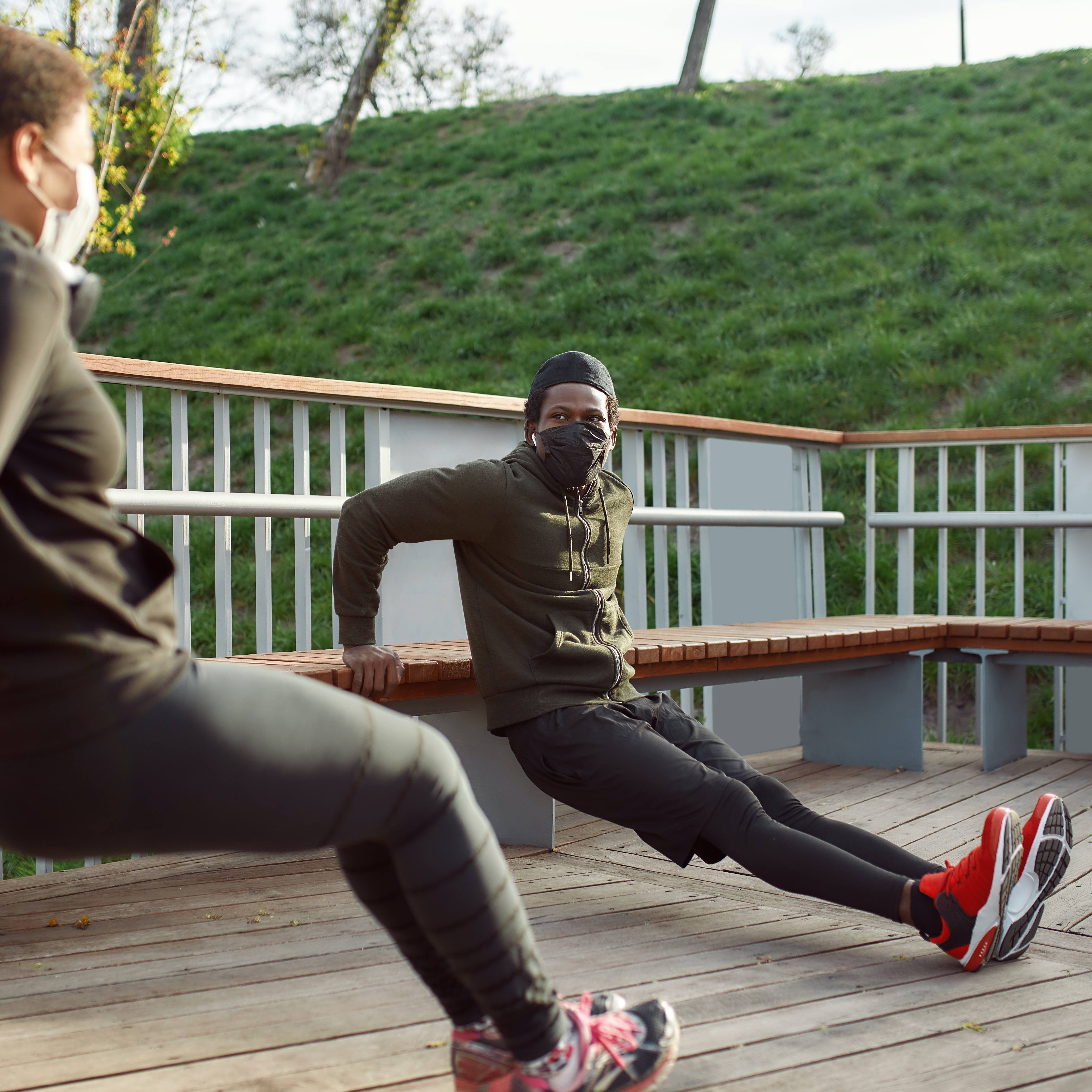 Two people working out while wearing masks