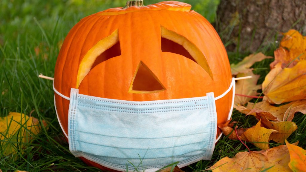 a carved Halloween pumpkin sitting out in the grass and leaves, wearing a PPE face mask