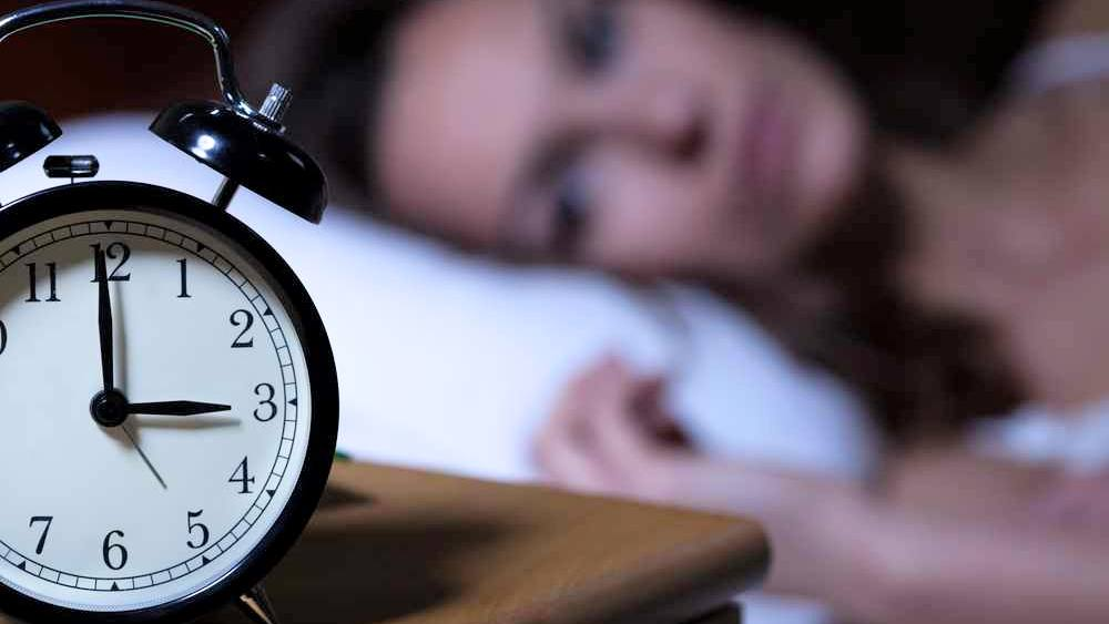 a close-up of an alarm clock reading 3 o'clock, with a wide awake woman lying on a pillow in the background, out of focus, trying to sleep and suffering from insomnia