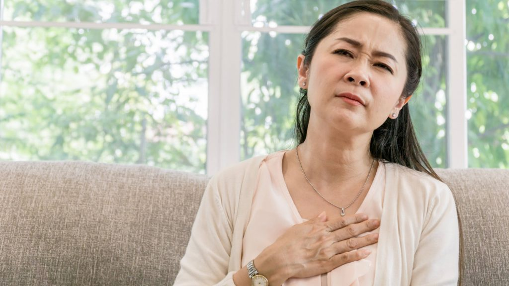 a middle aged Asian woman sitting on a couch near a window with her hand on her chest looking worried, sad, perhaps in pain