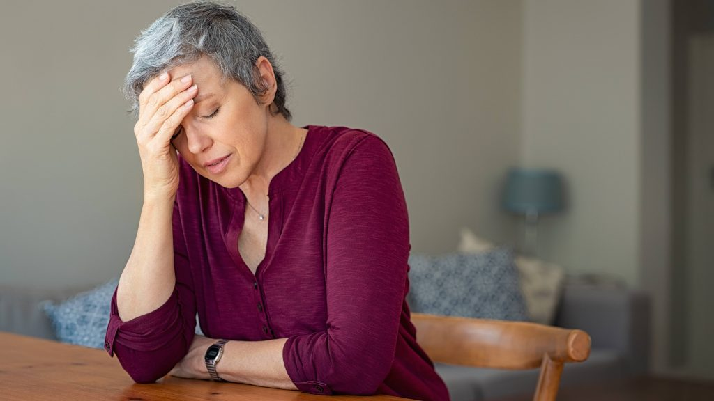 a middle aged white woman with slightly gray hair looking sad and worried, resting her head in her hand