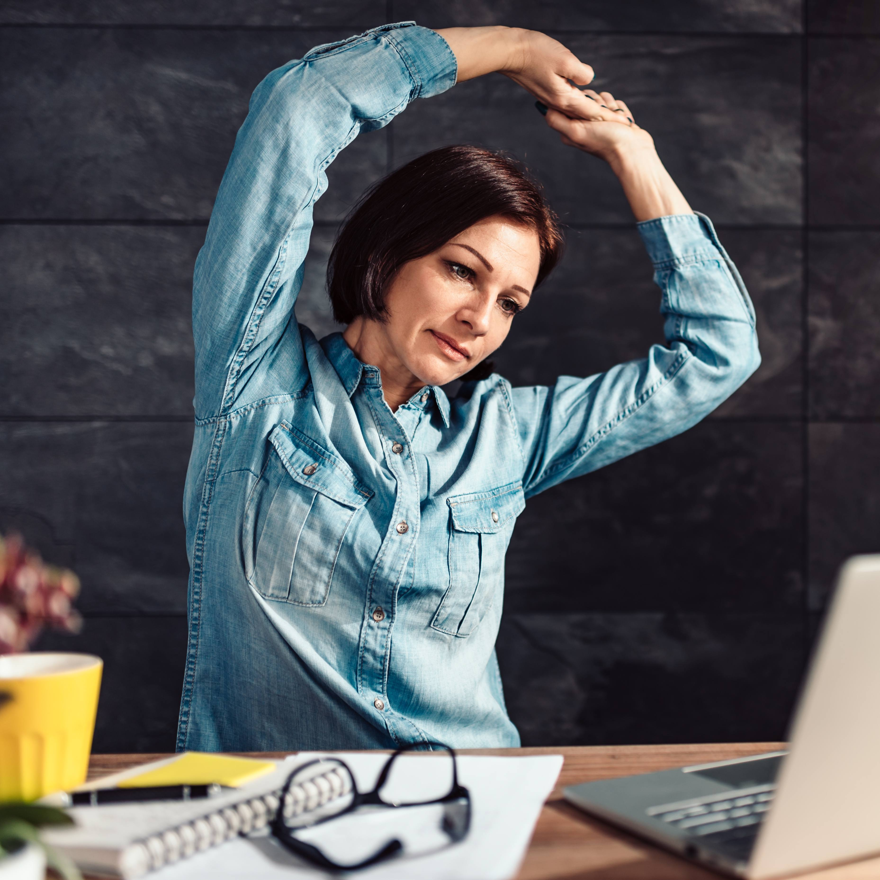 a white woman in a denim shirt sitting at a desk with a laptop, working and stretching her arms above her head to exercise