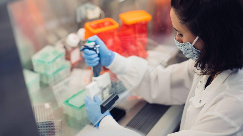 Mujer vistiendo una mascarilla y guantes médicos azules, trabajando en un laboratorio de investigación probando muestras de suero