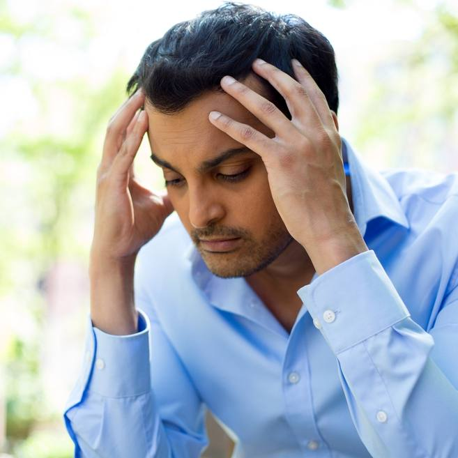 a young adult man, perhaps Latino, wearing a blue shirt and holding his head in his hands looking sad, stressed, depressed, unhappy