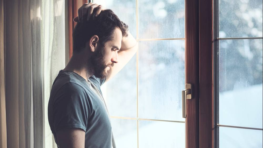 a young man standing by a rain-streaked window, looking sad, worried, depressed