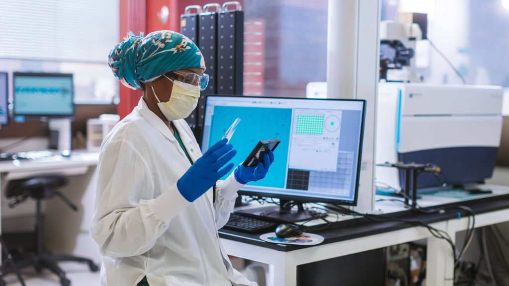 Mayo Clinic Laboratories health care researcher, a Black woman, wearing a hijab or scarf on her head and in PPE with a facemask, goggles and gloves looking at samples