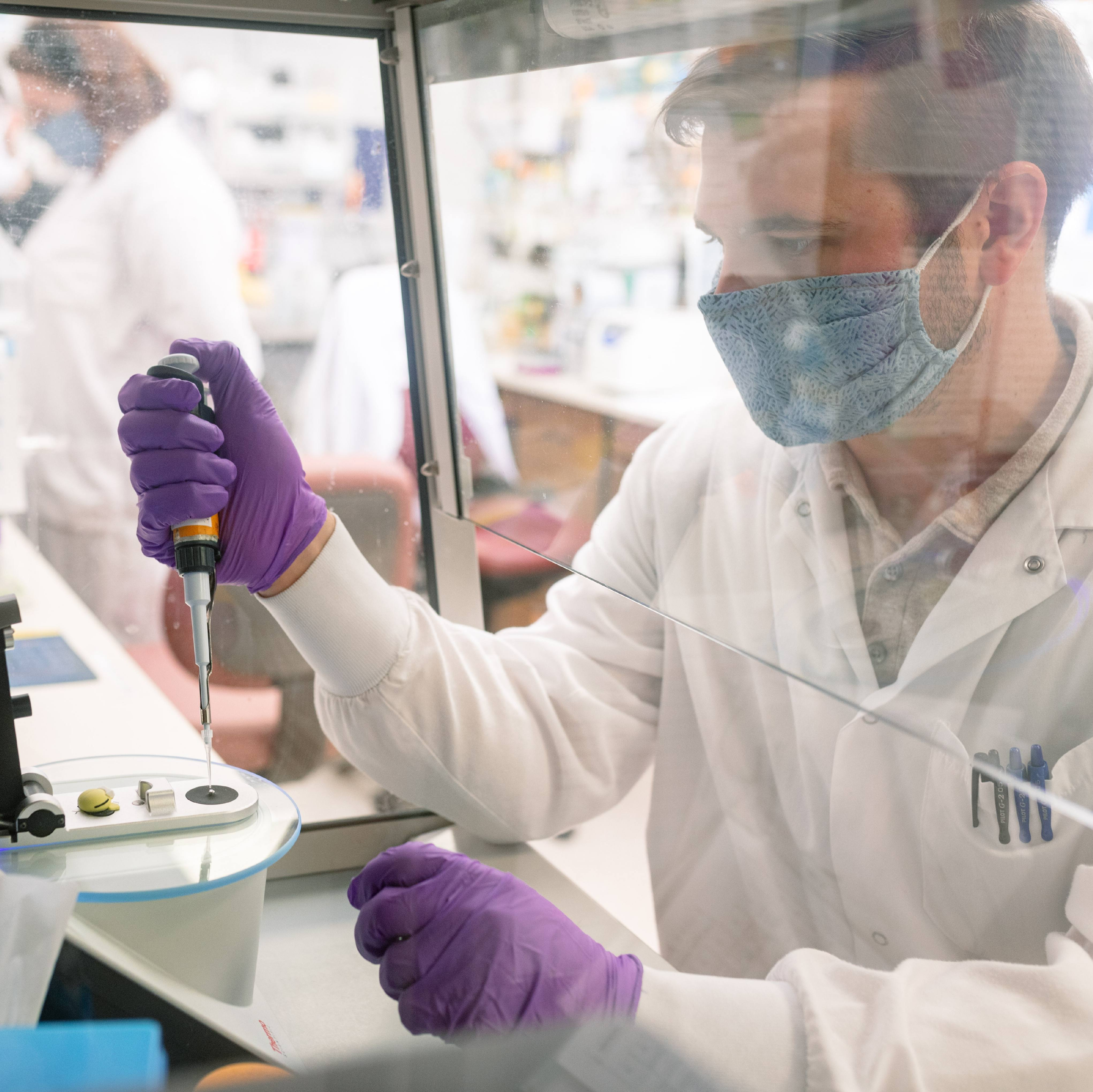 Mayo Clinic Laboratories researcher, a white man wearing a facemask and purple gloves while working with a specimen dropper behind a plastic shield in the lab