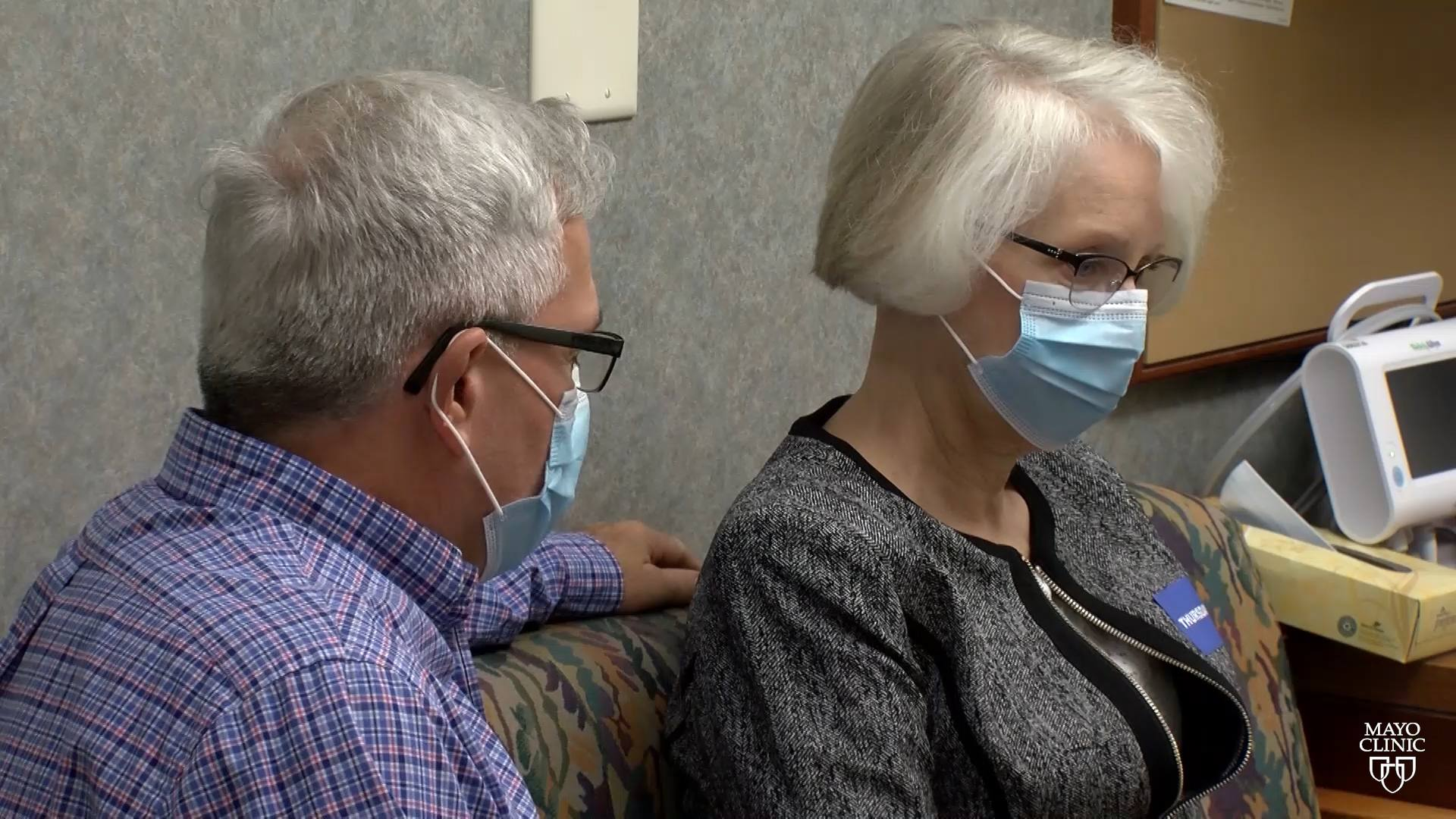 a middle aged woman with gray hair and eye glasses, wearing a mask, looking sad and sitting a physician's office