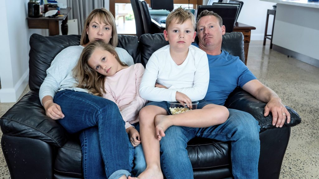 a family, a white woman and man sitting on a couch looking stressed, sad and tired, while holding their two white children on their laps