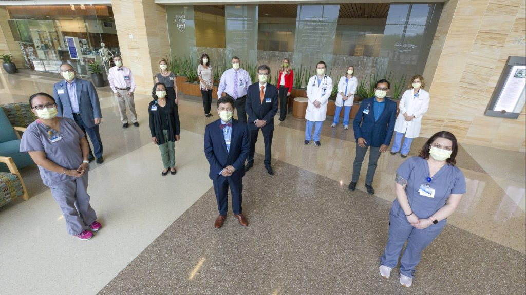 a large group of diverse people, Mayo Clinic medical staff members standing in a lobby wearing facemasks and practicing social distancing
