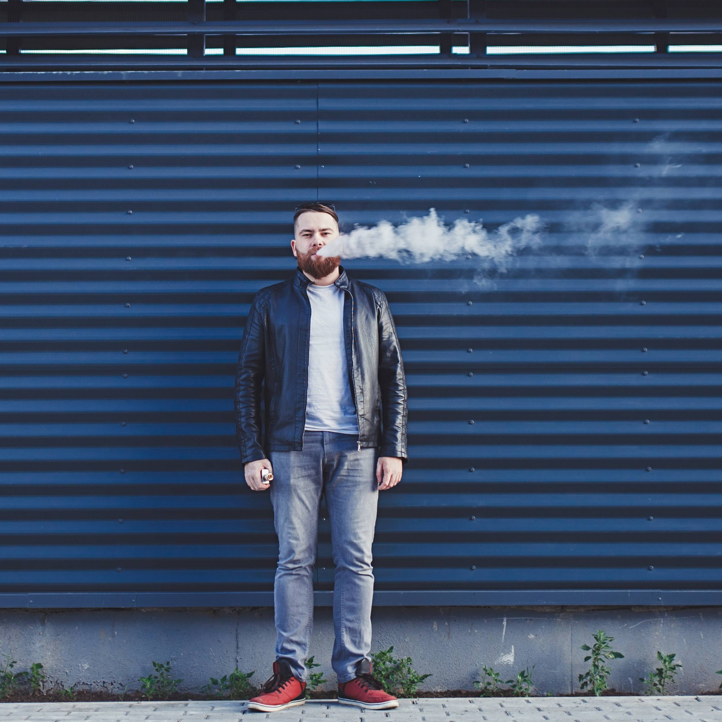 a white adult male in blue jeans standing outside in front of a blue metal building and smoking a cigarette or vaping