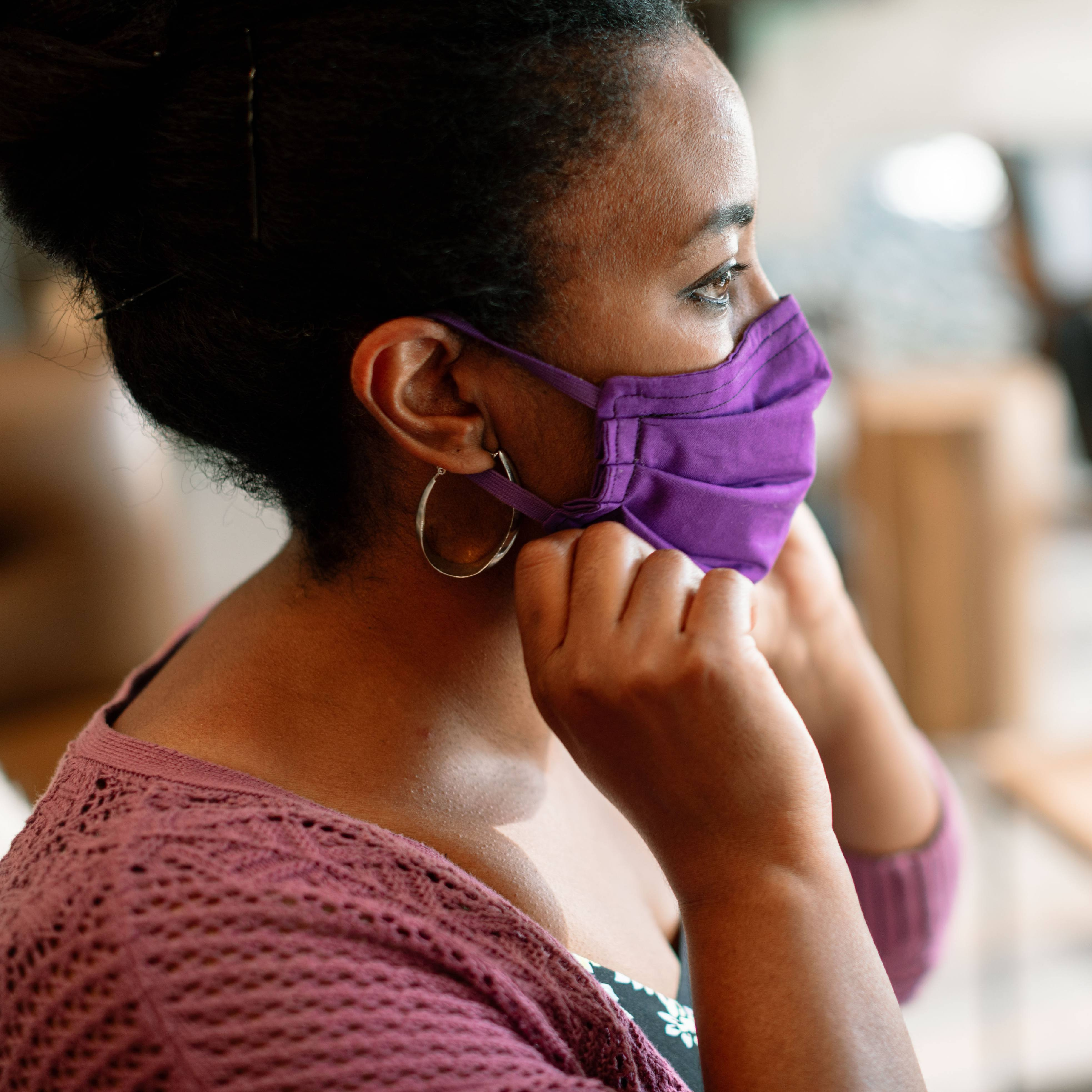 a young Black woman looking out a window and putting on a purple face mask