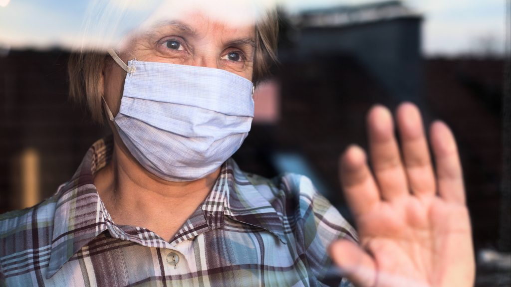 an elderly white woman wearing a face mask and holding her hand up on a window, looking outside and seeming sad, isolated