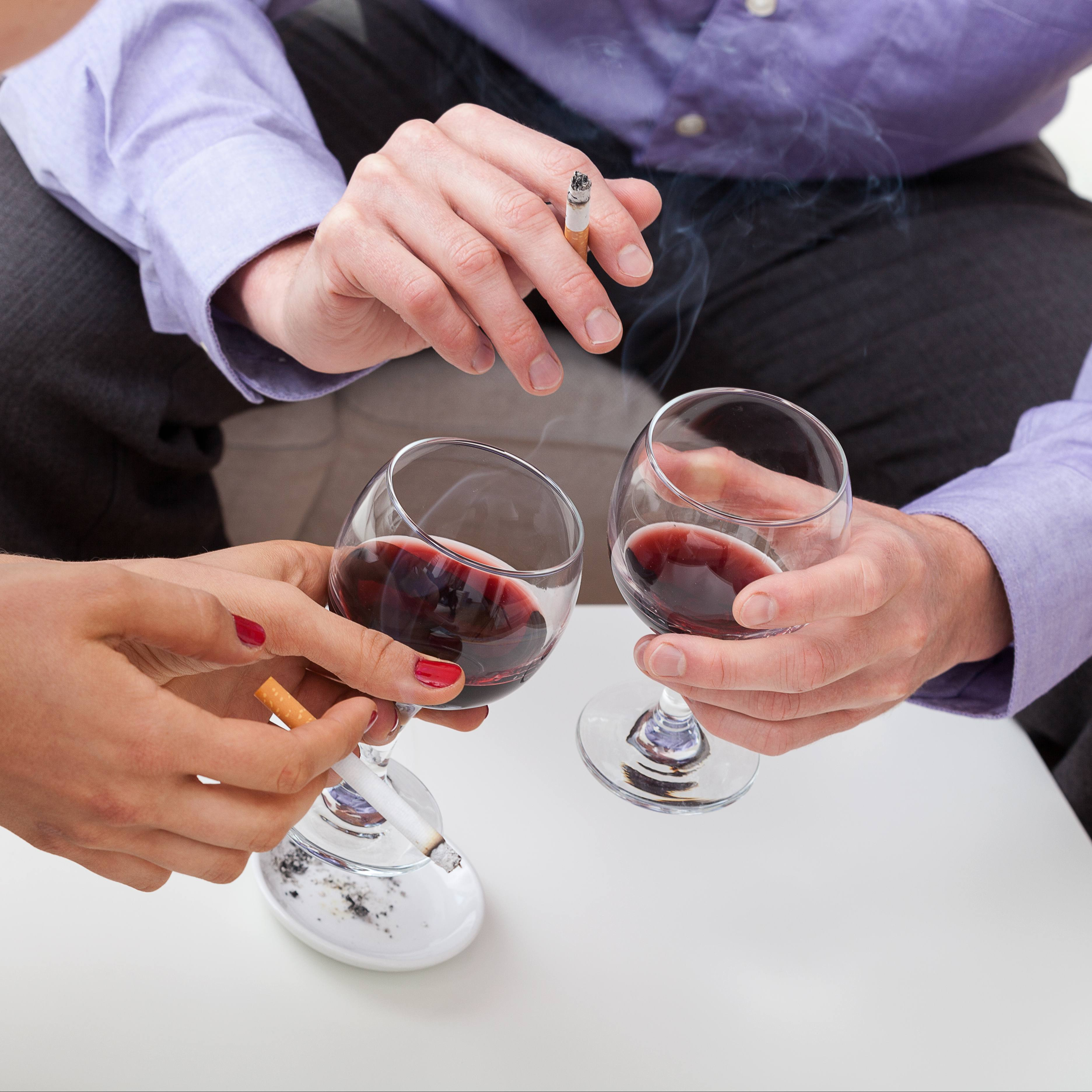 close up of the hands of two white people holding glasses of wine alcohol and tobacco cigarettes with smoke in the air