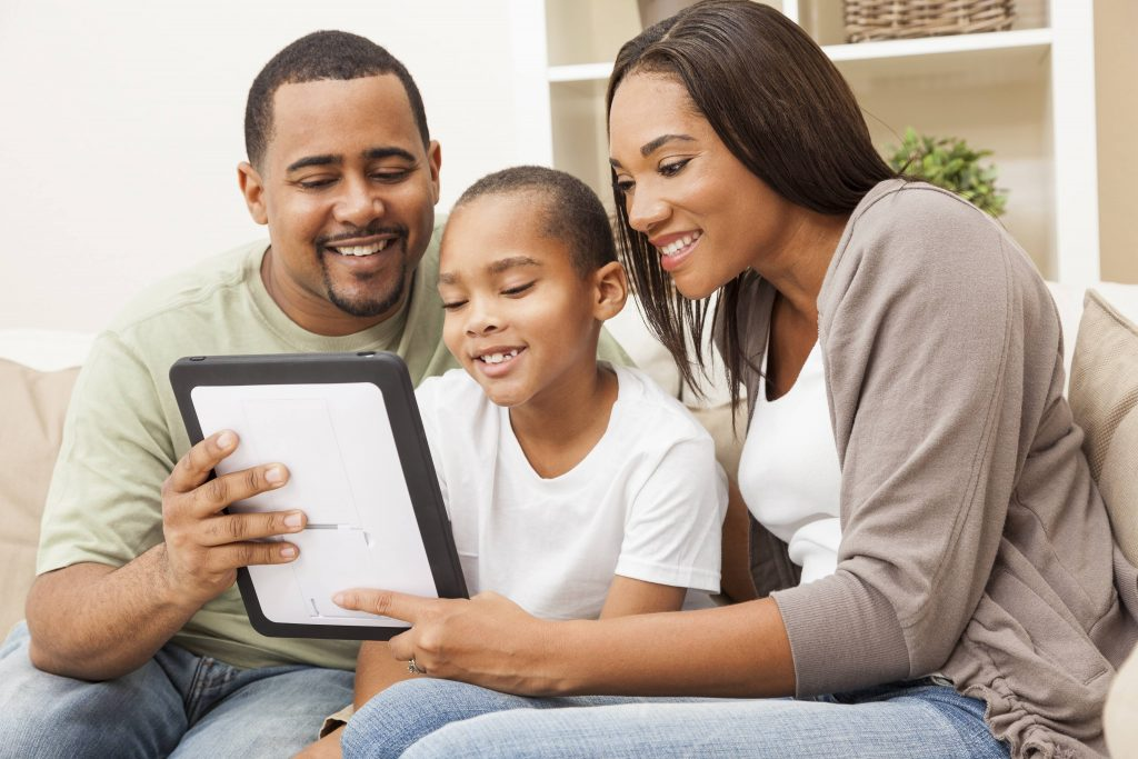 a young African American family, a Black man and Black woman, smiling and sitting on a couch with a young Black child looking at a computer tablet or iPad together
