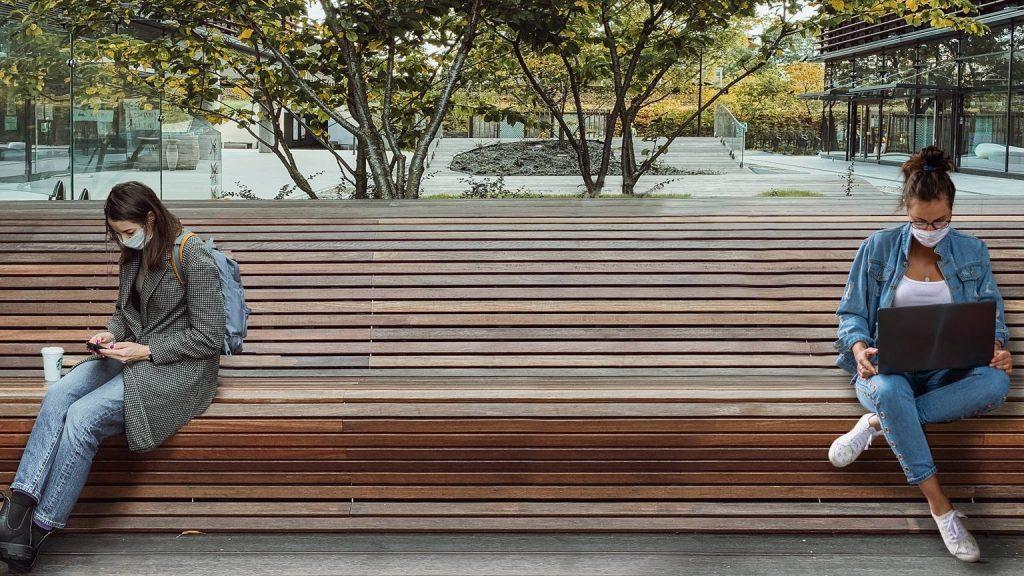 dos personas enmascaradas, sentadas a 6 pies de distancia en un banco