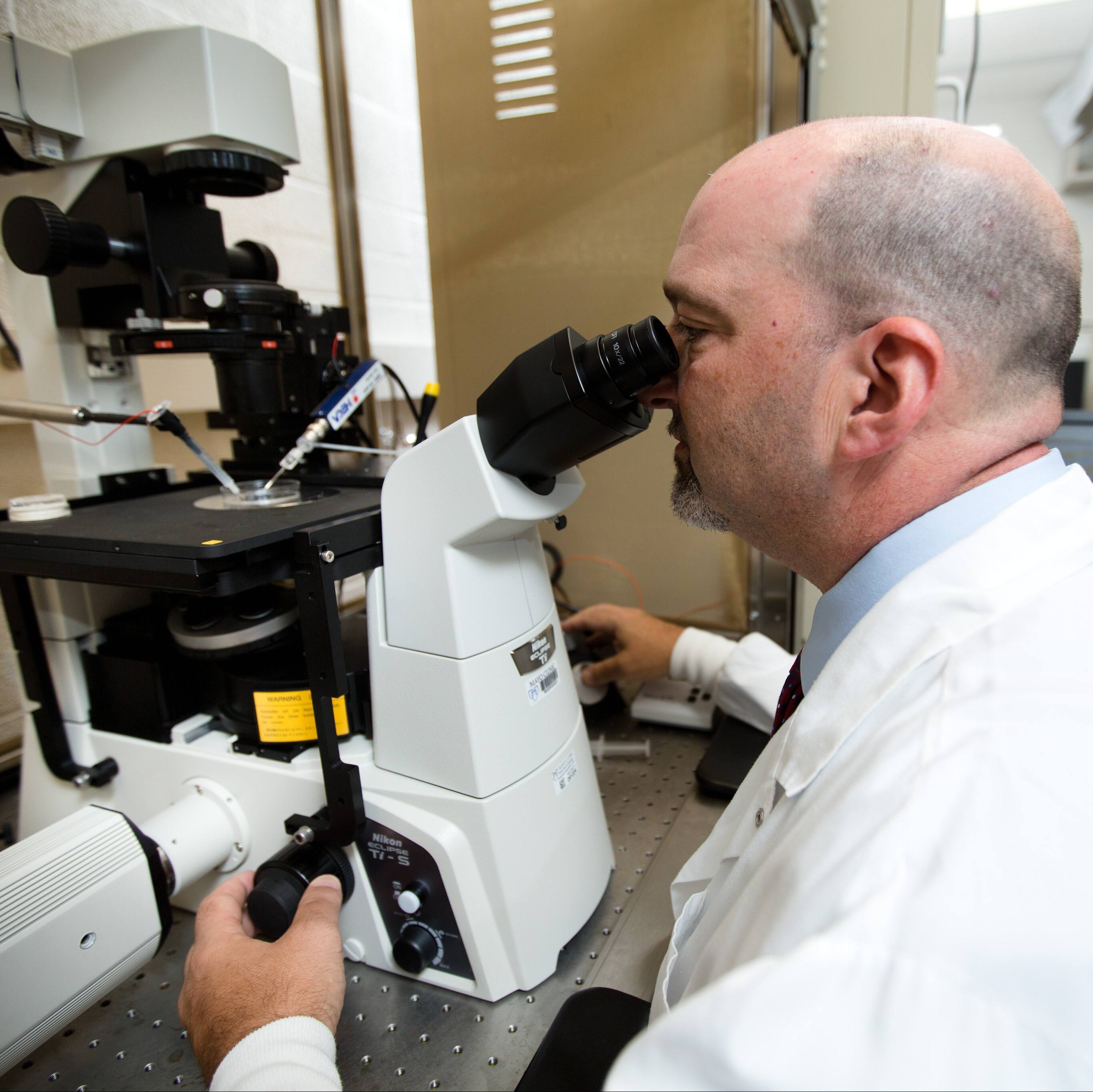 Alan Marmorstein, PhD a researcher looking through a microscope in a laboratory