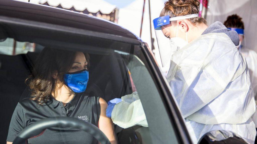 La Dra. Alyssa Chapital de Mayo Clinic con una mascarilla en su automóvil recibiendo la vacuna COVID-19 en Honor Health