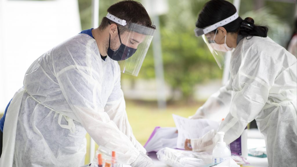 Mayo Clinic medical personnel in Florida, a white man and a white woman wearing PPE, preparing an outside table for drive-through COVID-19 testing