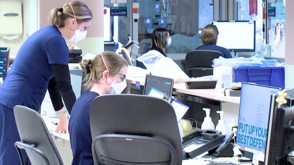 Mayo Clinic medical staff on the ICU floor, working on computer monitors and wearing facemasks
