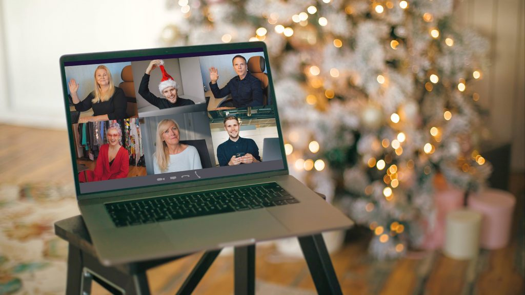 a computer laptop with a number of people in a virtual meeting, perhaps on Zoom, on a stool in front of a a decorated Christmas tree