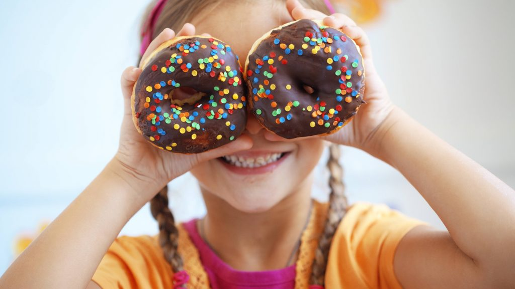 a young white girl with blonde braids holding sprinkle covered donuts over her eyes and smiling