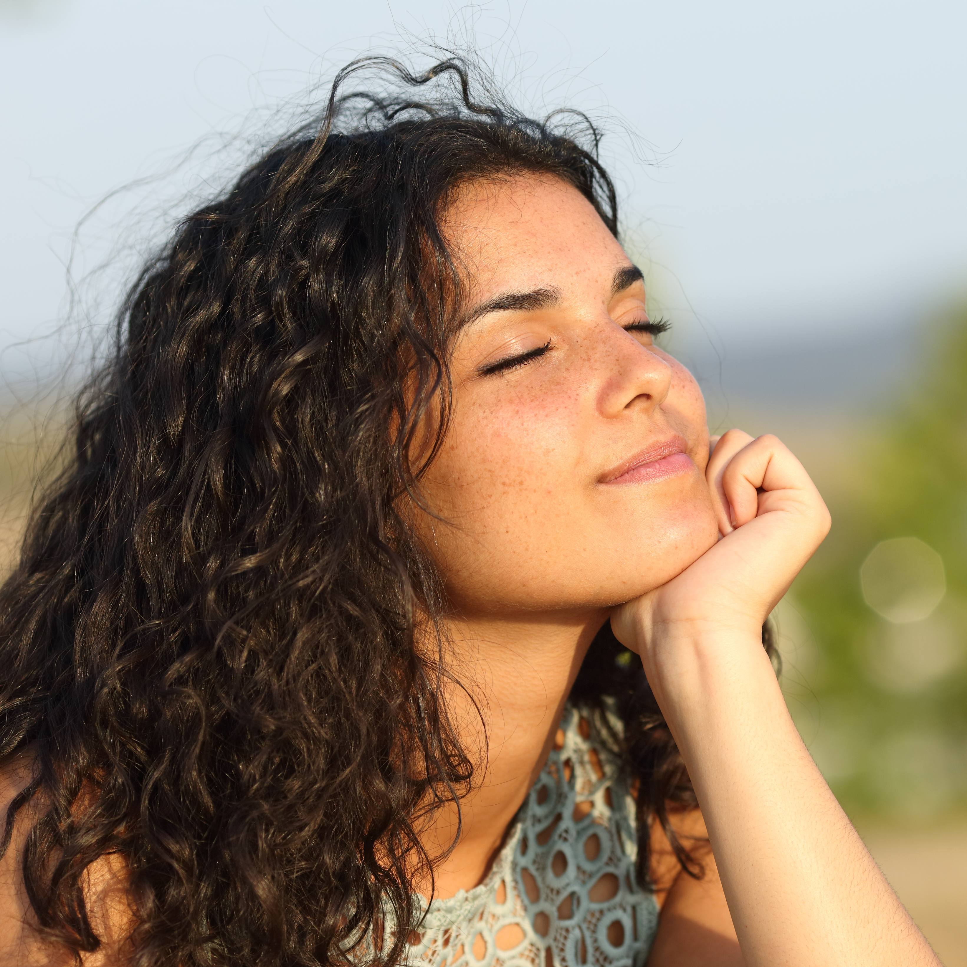 a young woman, perhaps older teenager, with light brown skin and long dark curly hair, smiling with her eyes closed and looking toward the sunshine