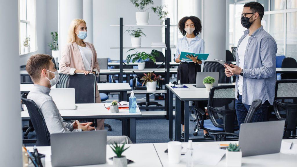 un grupo de jóvenes empresarios en una oficina con máscaras faciales y de pie a seis pies de distancia por el distanciamiento social COVID-19