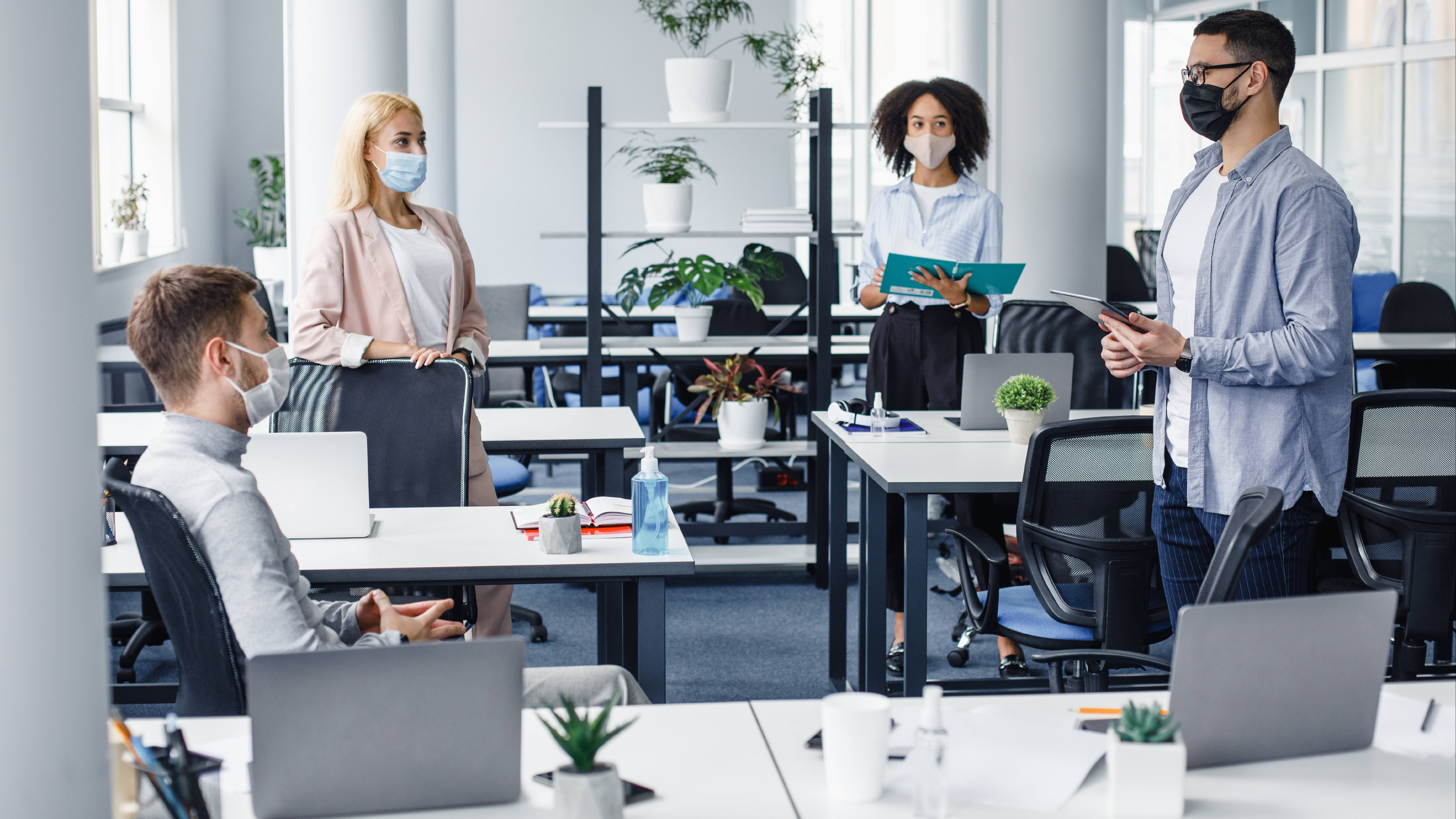 a group of young diverse students or business people in an office wearing face masks and standaing six feet apart for COVID-19 social distancing