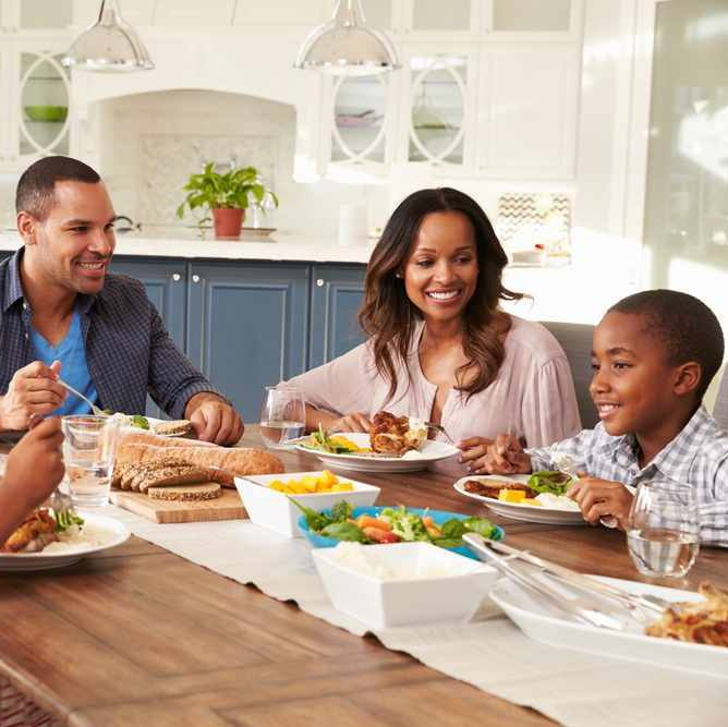 a young Black family, a man, woman, young girl and young boy, sitting at table laughing and smiling while eating a healthy meal together