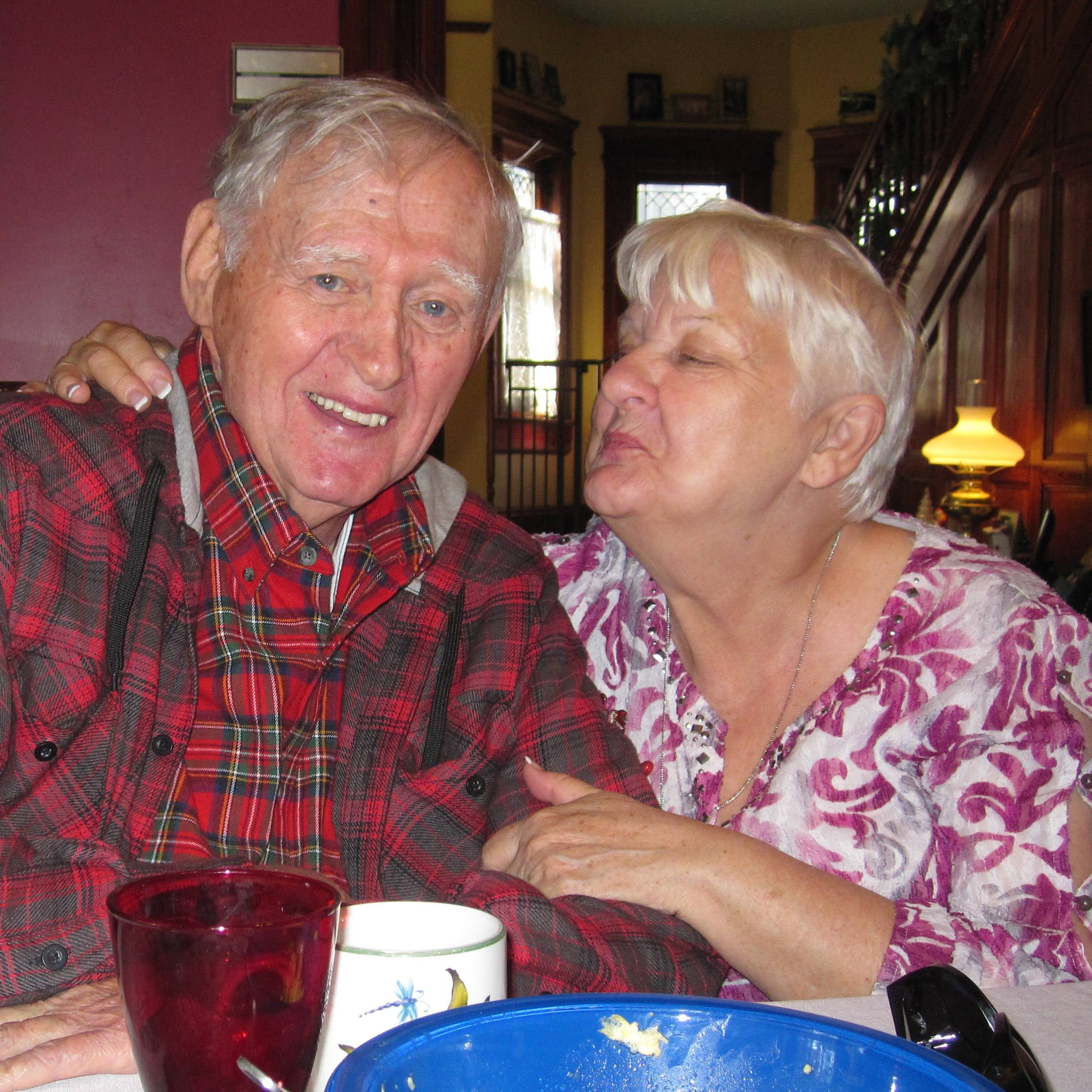 patient William Horne, a white man, sitting at a table in a plaid shirt and smiling with his wife, a white woman, hugging him