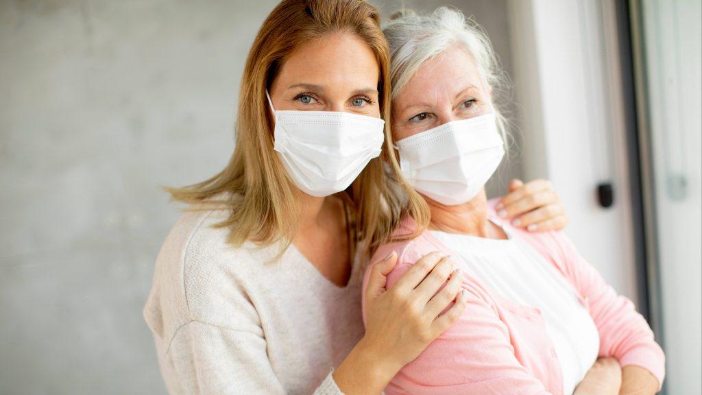 Dos mujeres, quizás madre con cabello gris e hija, con máscaras y de pie juntas cerca de una ventana