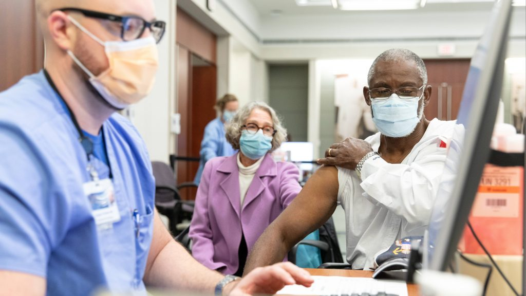 a Black adult man wearing PPE rolling up the sleeve of his white shirt for his COVID-19 vaccine