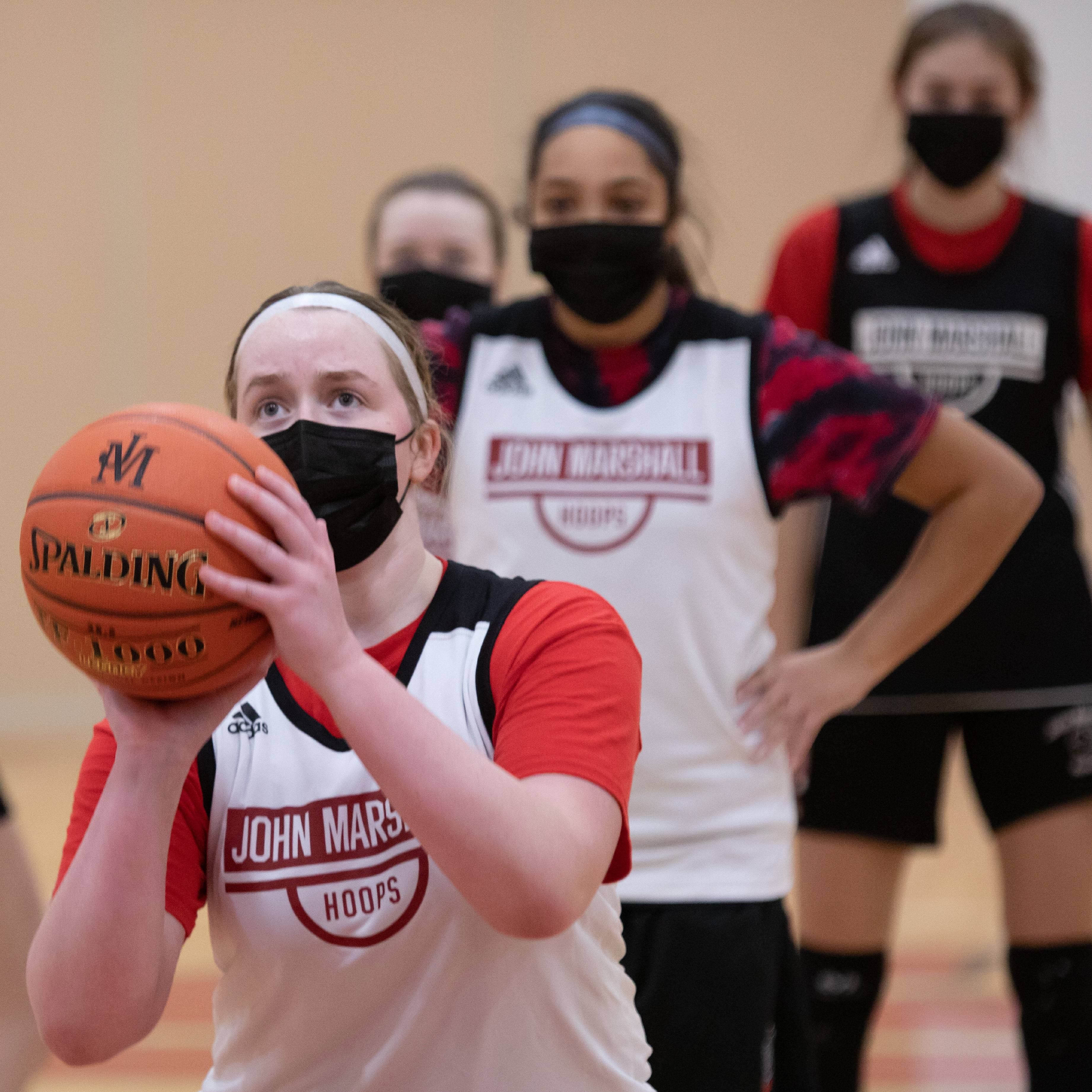 a diverse high school girls basketball team playing on a court in uniforms and wearing face masks