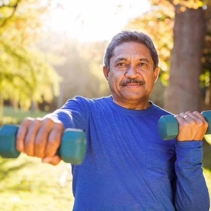 Portrait of mature man exercising with dumbbell at park