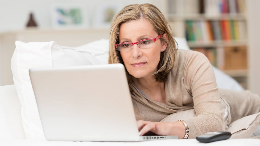 a middle-aged white woman wearing glasses and working on a laptop computer on her bed