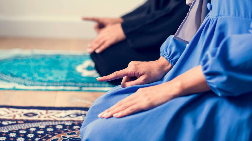 two people kneeling on a prayer rug and praying, perhaps during the Islamic Ramadan