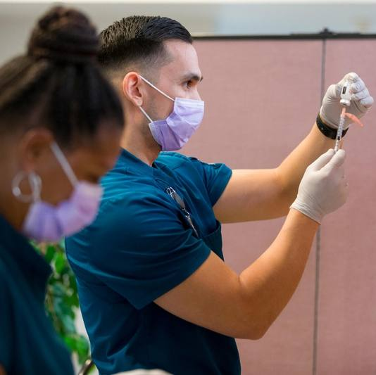 a white male and a Black woman, both Mayo Clinic nurses in scrubs prepare COVID-19 vaccine syringes