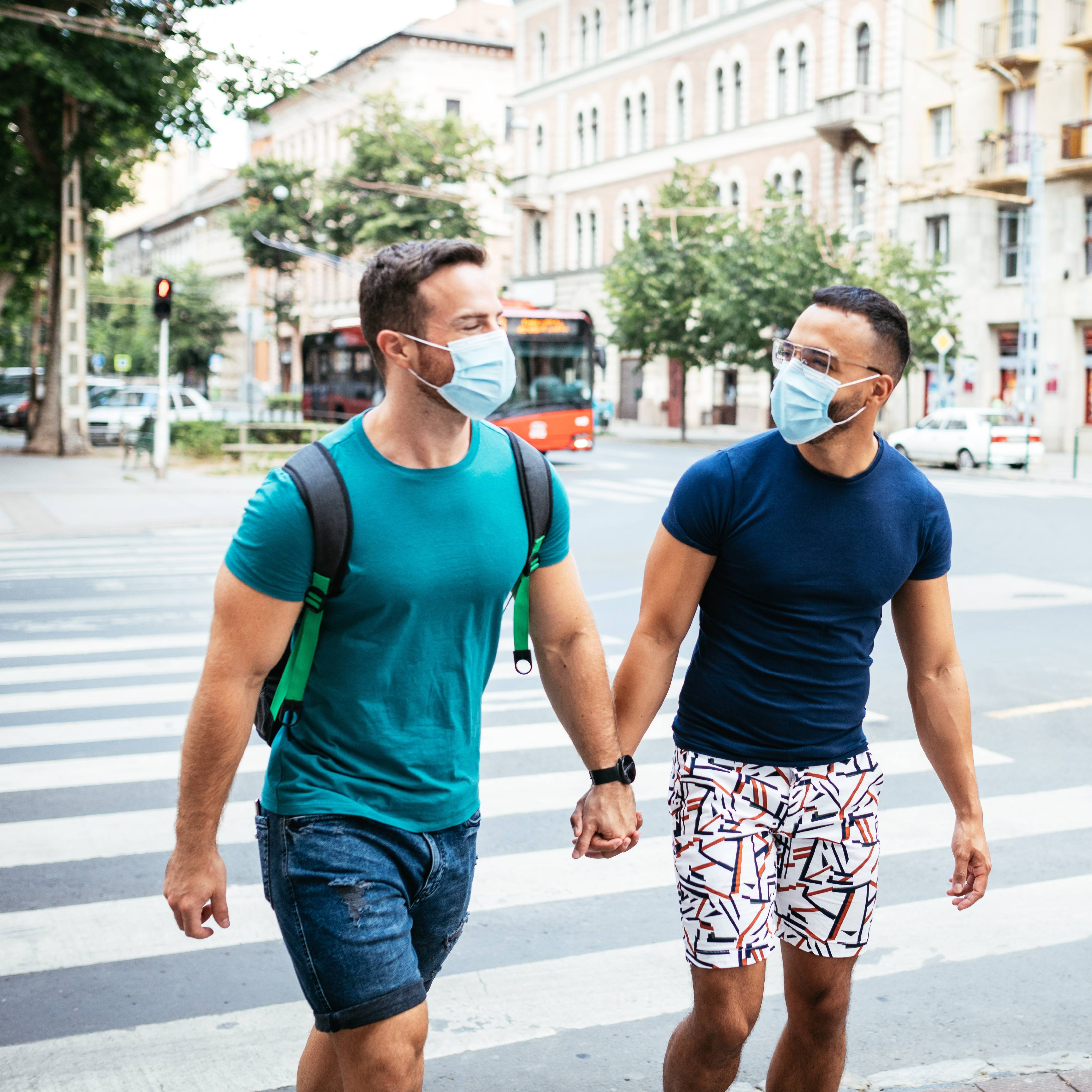 a gay couple walking together on a street, holding hands and wearing face masks